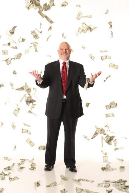 Man standing in shower of paper money
