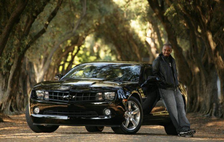 Proud man with shiny black sedan