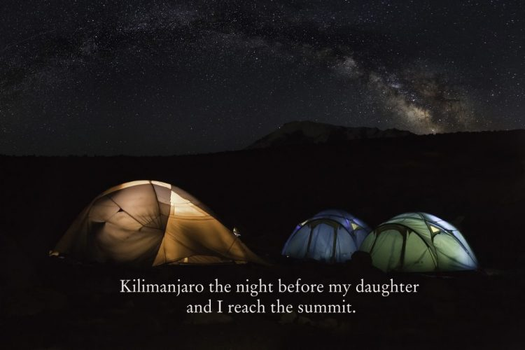 Starry night sky with mountain peak and tents lit from inside